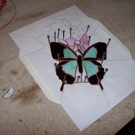 Travail en cours sur un vitrail tiffany représentant un papillon