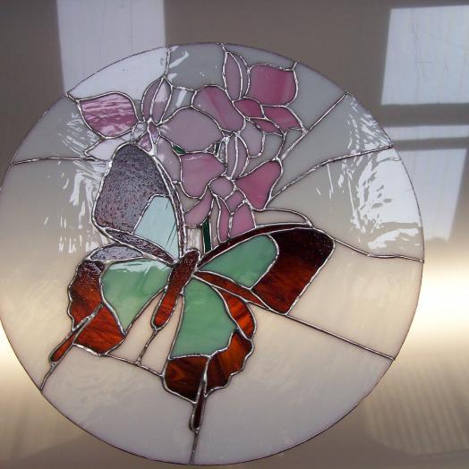 Papillon et fleur sur un vitrail tiffany rond