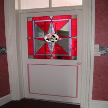 Vitrail sur une porte avec un papillon au milieu